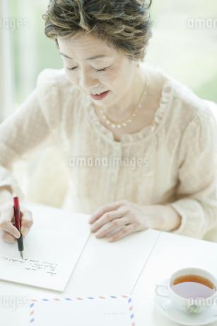 リビングで手紙を書く中高年女性の写真素材 [FYI02510956]