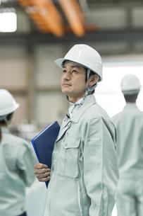 上を見上げる作業員男性の写真素材 [FYI02510966]