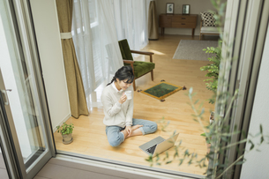 窓辺でパソコンを見る若い女性の写真素材 [FYI02510980]