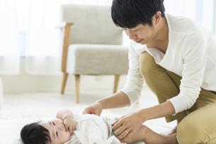 赤ちゃんのおむつを替える父親の写真素材 [FYI02511037]