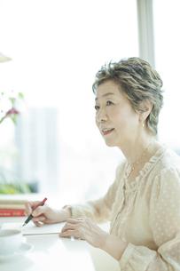 リビングで手紙を書く中高年女性の写真素材 [FYI02511041]
