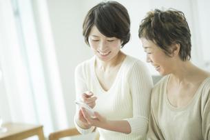スマートフォンを見る母と娘の写真素材 [FYI02511050]