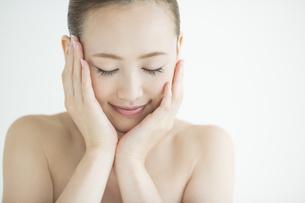 両手で顔を包み込む女性のスキンケアイメージの写真素材 [FYI02511154]