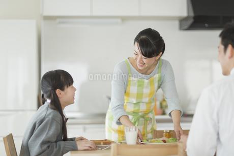 朝食中の家族と会話をする母親の写真素材 [FYI02511259]