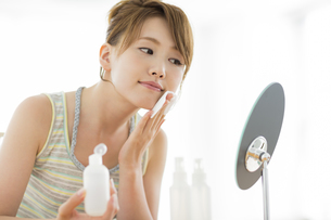 コットンを頬にあてて鏡を見る女性の写真素材 [FYI02511359]