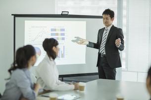 プロジェクターを使用した会議で説明をするビジネスマンの写真素材 [FYI02511377]