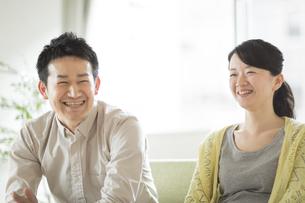 ソファーに座って会話をする夫婦の写真素材 [FYI02511390]