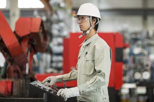 機械を操作する作業服の男性の写真素材 [FYI02511411]