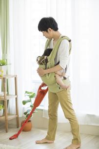赤ちゃんを抱っこしながら掃除機をかける父親の写真素材 [FYI02511418]