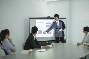 プロジェクターを使用した会議で説明をするビジネスマンの写真素材 [FYI02511471]