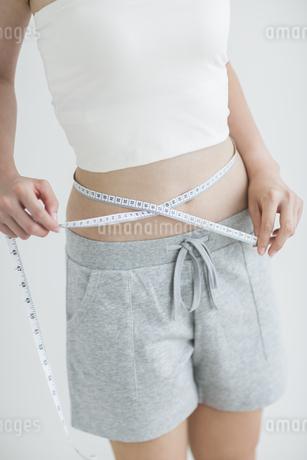 メジャーでウエストを測る女性の写真素材 [FYI02511533]