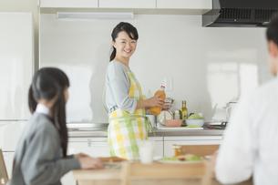 朝食中の家族と会話をする母親の写真素材 [FYI02511637]
