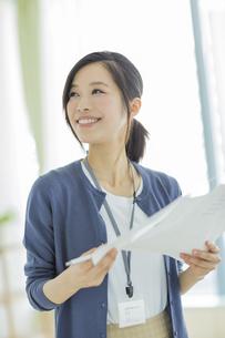 書類を持つ笑顔のビジネスウーマンの写真素材 [FYI02511667]