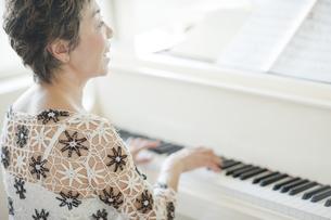 ピアノを弾き歌を歌う中高年女性の写真素材 [FYI02511674]
