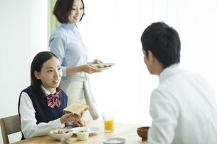 朝食中に会話をする家族の写真素材 [FYI02511692]