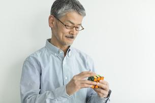 ルービックキューブを持つシニア男性の写真素材 [FYI02511739]