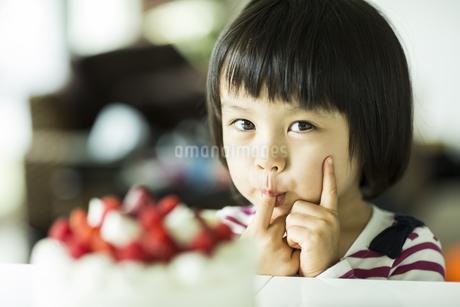 ケーキのクリームを舐める女の子の写真素材 [FYI02511747]