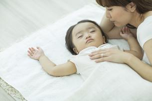 眠る赤ちゃんを見守る母親の写真素材 [FYI02511798]