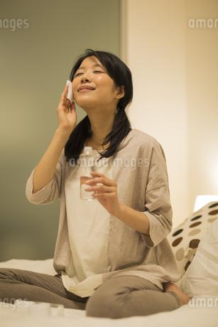 ベッドの上でスキンケアをする女性の写真素材 [FYI02511836]