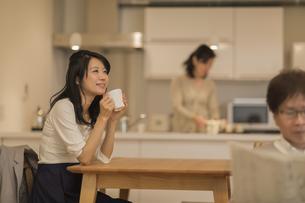 ダイニングテーブルでお茶を飲む娘の写真素材 [FYI02511850]