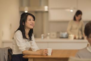 ダイニングテーブルでお茶を飲む娘の写真素材 [FYI02511859]