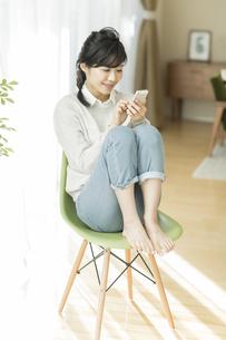 椅子に座って携帯電話を見る女性の写真素材 [FYI02511886]