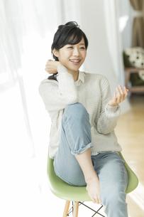 椅子に座る笑顔の女性の写真素材 [FYI02511894]