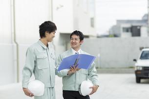打ち合わせをする2人の作業着の男性の写真素材 [FYI02511916]