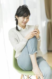 椅子に座って携帯電話を見る女性の写真素材 [FYI02511924]
