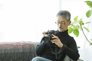 一眼レフカメラを触るシニア男性の写真素材 [FYI02512304]