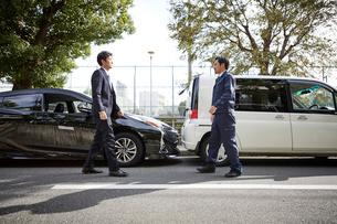 2台の車と歩み寄る二人の男性の写真素材 [FYI02512327]