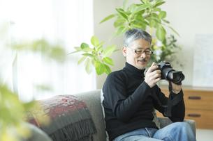 一眼レフカメラを触るシニア男性の写真素材 [FYI02512476]