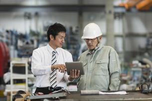 タブレットPCを見ながら打ち合わせをする作業員とビジネスマンの写真素材 [FYI02512510]