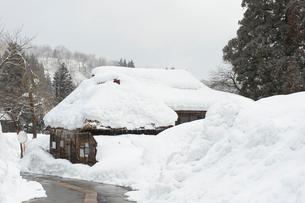 雪の中の民家と道路の写真素材 [FYI02512538]