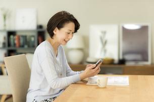 スマートフォンを操作するシニア女性の写真素材 [FYI02512557]