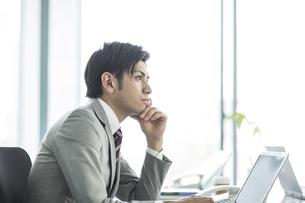 頬杖をついて考えるビジネスマンの写真素材 [FYI02512569]