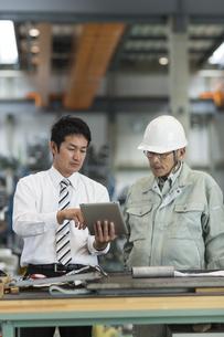 タブレットPCを見ながら打ち合わせをする作業員とビジネスマンの写真素材 [FYI02512588]