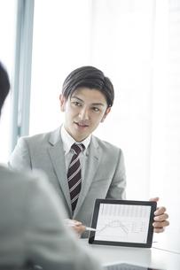 タブレットPCを使用して打ち合わせをするビジネスマンの写真素材 [FYI02512605]