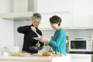 キッチンで調理をするシニア夫婦の写真素材 [FYI02512649]