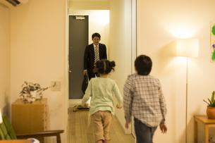 帰宅した父親に駆け寄る子供たちの写真素材 [FYI02512655]