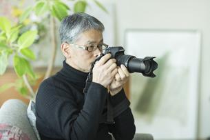 一眼レフカメラを触るシニア男性の写真素材 [FYI02512672]