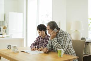 パンフレットを見ながら電話をかけるシニア夫婦の写真素材 [FYI02512674]