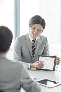 タブレットPCを使用して打ち合わせをするビジネスマンの写真素材 [FYI02512717]