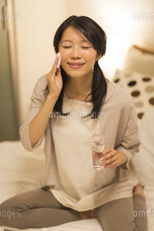 ベッドの上でスキンケアをする女性の写真素材 [FYI02512747]