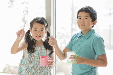 歯ブラシとコップを持って笑顔の兄と妹の写真素材 [FYI02512819]