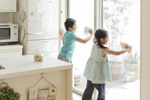 窓拭きをする兄と妹の写真素材 [FYI02512823]