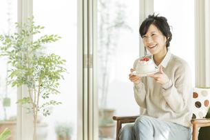 ケーキを持って笑顔の女性の写真素材 [FYI02512877]