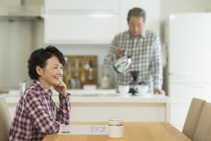 テーブルに座り笑顔のシニア女性の写真素材 [FYI02512921]