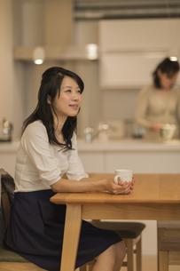 ダイニングテーブルでお茶を飲む娘の写真素材 [FYI02512936]
