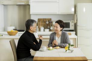 テーブルで会話をするシニア夫婦の写真素材 [FYI02512938]